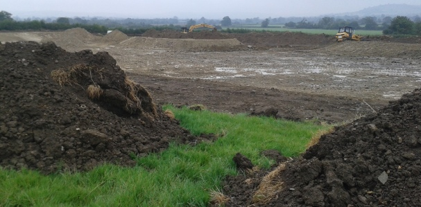 From south west corner showing island with digger behind